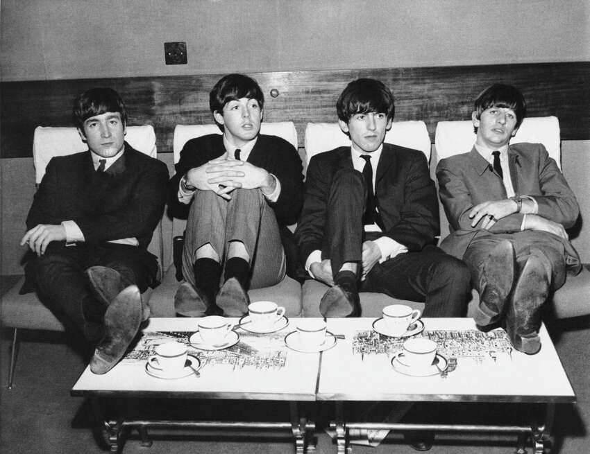 The Beatles, Britain's top rock band, relax in London over tea in 1963. The group from left: John Lennon, Paul McCartney; George Harrison and Ringo Starr. The group is sporting similar thatch haircuts with bangs to the edge of their eyebrows. No other information available with photo. (AP Photo)
