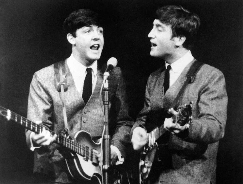 Paul McCartney, left, and John Lennon, two members of the Beatles pop group during a concert in London, on Nov. 11, 1963. (AP Photo/N)