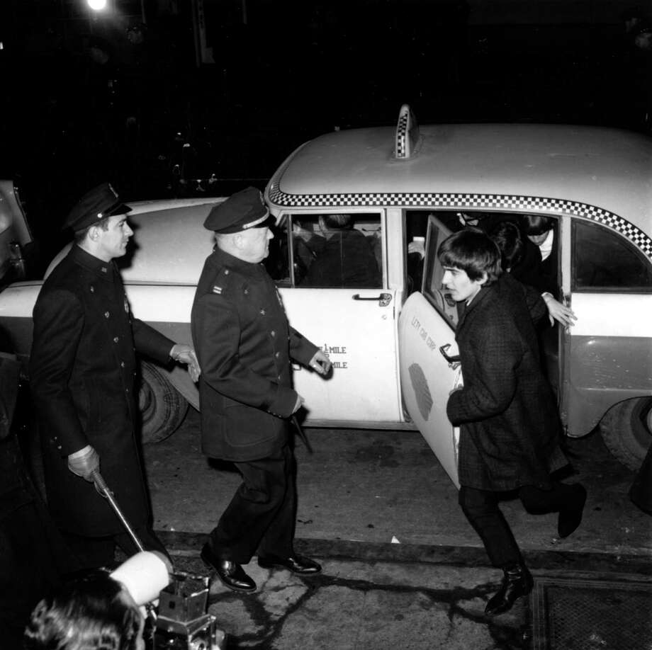 Police security is on hand for the arrival of The Beatles as guitarist George Harrison leads the way from a taxi-cab to Carnegie Hall's stagedoor on W. 56th St. in New York City on Feb. 12, 1964 .  About 2,000 fans are gathered outside the concert hall to catch a glimpse of the British rock and roll band on their first U.S. tour. Photo: ASSOCIATED PRESS / Associated Press