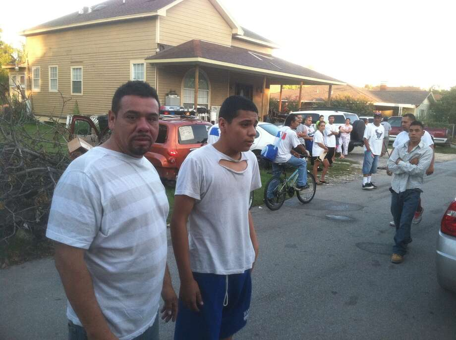 Jose Rosas Sr. and his son watch firefighters at their burned apartment. (Dale Lezon/Chornicle)