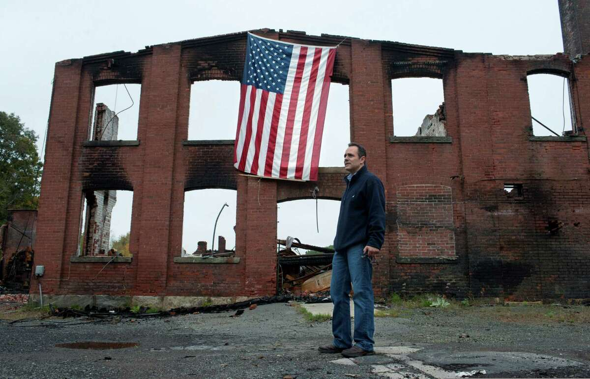 Matt Bevin stands at the site of his family's factory destroyed by fire in East Hampton, Conn., Wednesday, Oct. 3, 2012. The 180-year-old New England company that made the tiny bell that tinkles every time an angel gets its wings in the holiday classic