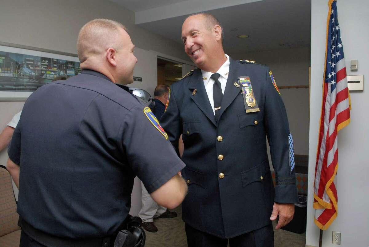 Stamford Mayor Michael A. Pavia announces that Jonathan Fontneau is Stamford's next Chief of Police in Stamford, Conn. on Friday October 5, 2012. Fontneau is congratulated by a fellow officer.