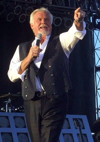 Kenny Rogers points to the crowd while performing in this July 30, 2003 file photo, at the South Dakota State Fair in Huron, S.D. A tiny western Indiana town is organizing a concert featuring country music stars Rogers, Sarah Evans and Ricky Van Shelton to raise money to revive the community. The town of Waveland, population about 500, will use the proceeds of the June 5, 2004, concert to repair sidewalks, install streetlights and improve playgrounds, said Brenda Jones, one of the organizers. Photo: ERIC JOHNSON, AP / HURON PLAINSMAN