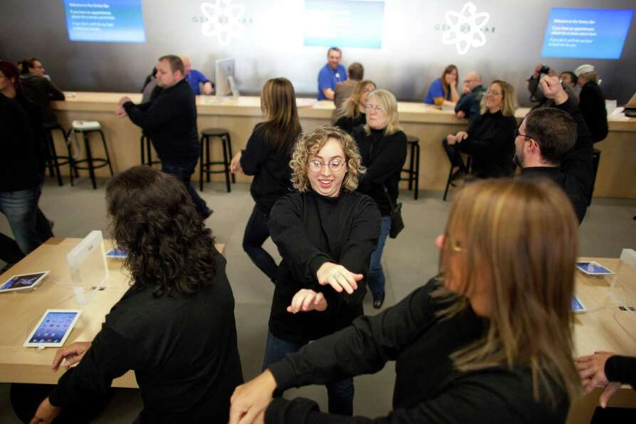 People dance to Gangnam Style during a flash mob honoring Apple co-founder Steve Jobs on Friday, Oct