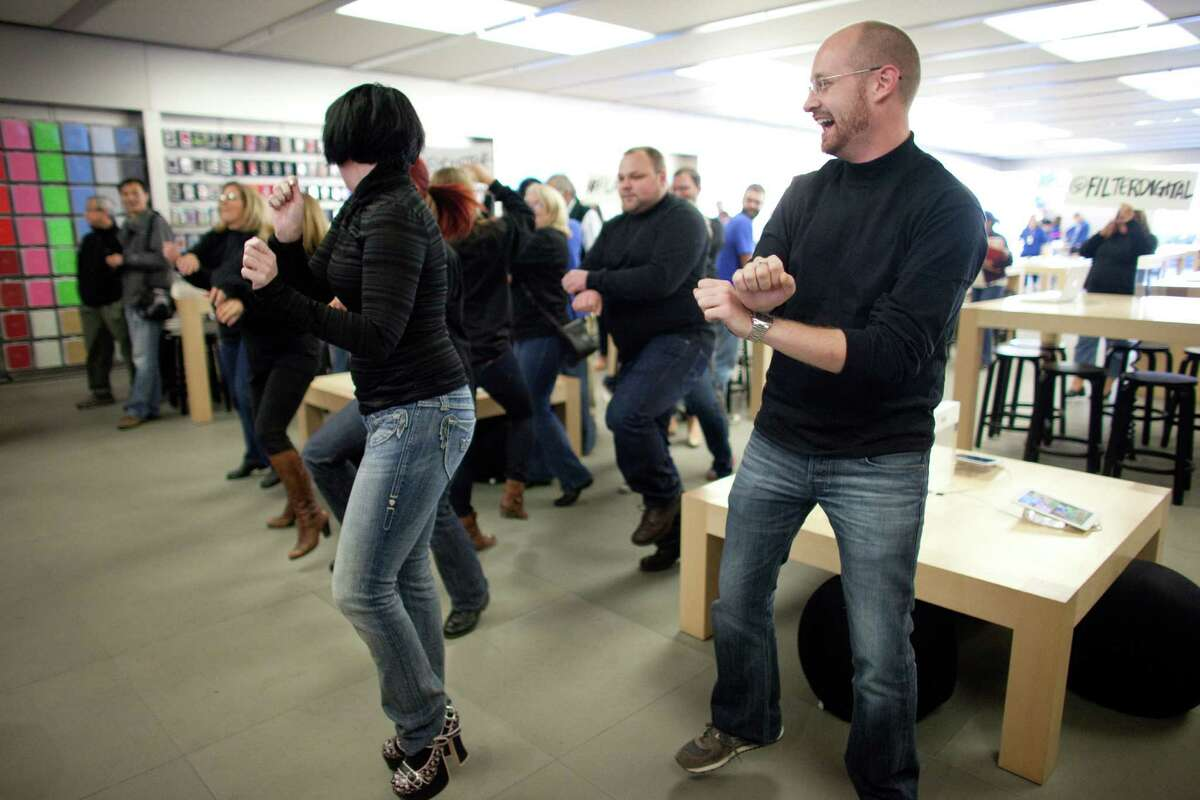 People dance to Gangnam Style during a flash mob honoring Apple co-founder Steve Jobs on Friday at the University Village Apple Store in Seattle. October 5 is the one-year anniversary of the death of the innovative technology leader. The flash mob was organized by Filter digital agency and participants wore Jobs' signature black turtlenecks, jeans and glasses. The event payed homage to Jobs' quote during a 2005 speech at Stanford University: