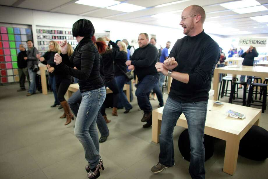 "People dance to Gangnam Style during a flash mob honoring Apple co-founder Steve Jobs on Friday at the University Village Apple Store in Seattle. October 5 is the one-year anniversary of the death of the innovative technology leader. The flash mob was organized by Filter digital agency  and participants wore Jobs' signature black turtlenecks, jeans and glasses. The event payed homage to Jobs' quote during a 2005 speech at Stanford University: ""Stay hungry, Stay foolish!"" Photo: JOSHUA TRUJILLO / SEATTLEPI.COM"