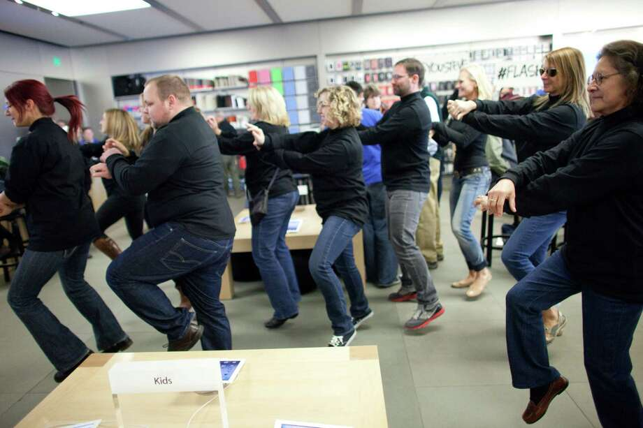 "People dance to Gangnam Style during a flash mob honoring Apple co-founder Steve Jobs on Friday at the University Village Apple Store in Seattle. Oct. 5 is the one-year anniversary of the death of the innovative technology leader. The flash mob was organized by Filter digital agency  and participants wore Jobs' signature black turtlenecks, jeans and glasses. The event payed homage to Jobs' quote during a 2005 speech at Stanford University: ""Stay hungry, Stay foolish!"" Photo: JOSHUA TRUJILLO / SEATTLEPI.COM"