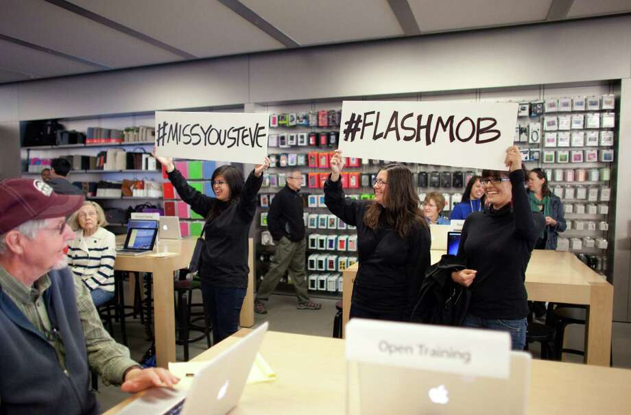 "Participants hold up signs during a flash mob honoring Apple co-founder Steve Jobs on Friday at the University Village Apple Store in Seattle. October 5 is the one-year anniversary of the death of the innovative technology leader. The flash mob was organized by Filter digital agency  and participants wore Jobs' signature black turtlenecks, jeans and glasses. The event payed homage to Jobs' quote during a 2005 speech at Stanford University: ""Stay hungry, Stay foolish!"" Photo: JOSHUA TRUJILLO / SEATTLEPI.COM"