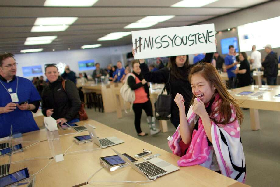 "A customer laughs as people dance to Gangnam Style during a flash mob honoring Apple co-founder Steve Jobs on Friday at the University Village Apple Store in Seattle. October 5 is the one-year anniversary of the death of the innovative technology leader. The flash mob was organized by Filter digital agency  and participants wore Jobs' signature black turtlenecks, jeans and glasses. The event payed homage to Jobs' quote during a 2005 speech at Stanford University: ""Stay hungry, Stay foolish!"" Photo: JOSHUA TRUJILLO / SEATTLEPI.COM"