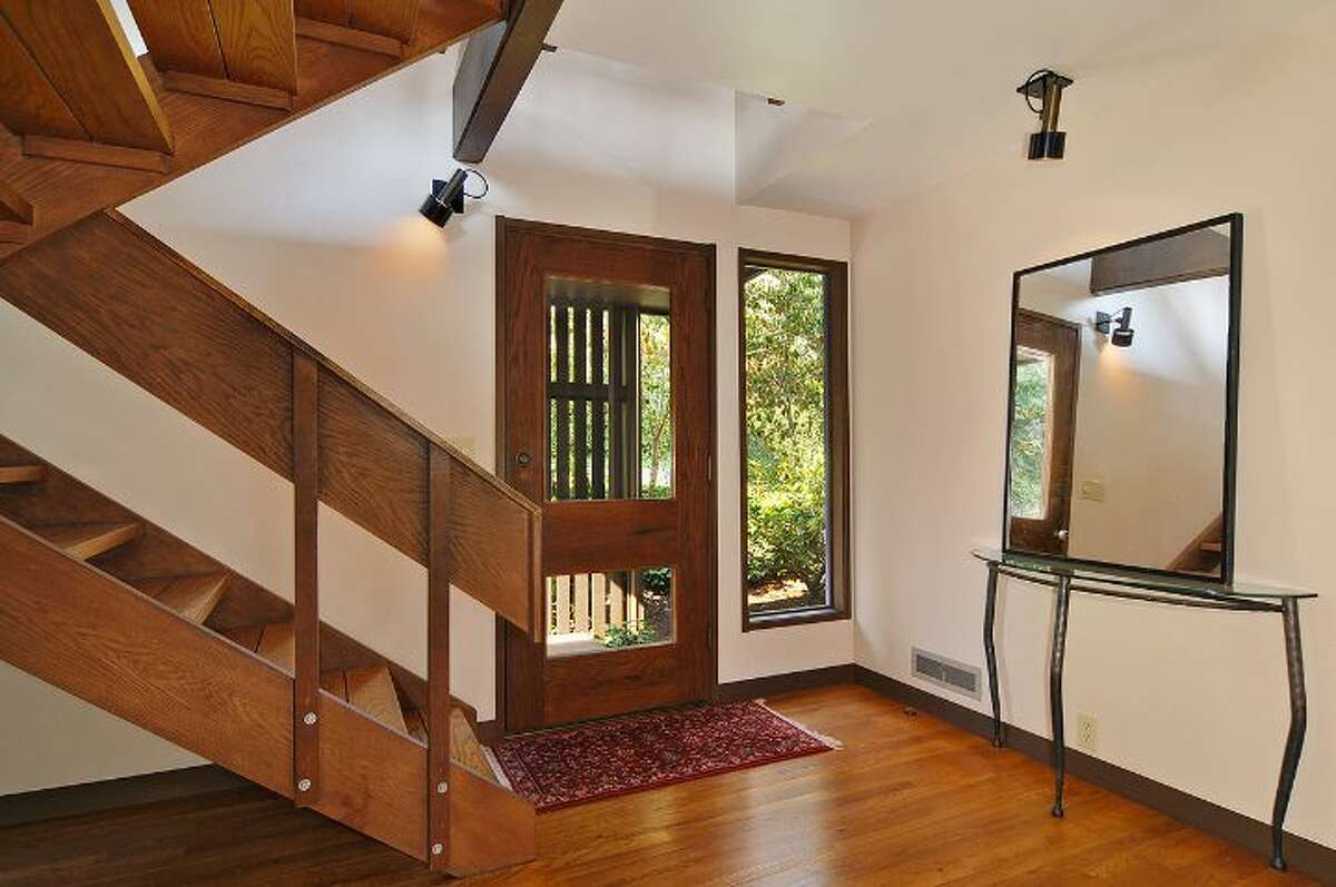 Foyer of 411 Erie Ave., in Leschi. The 2,440-square-foot house, built in 1970, has three bedrooms, two bathrooms, wood doors, moldings, stairways, ceilings and beams, walls of windows looking over Lake Washington, along with a view deck on a 6,600-square-foot lot. It's listed for $850,000.