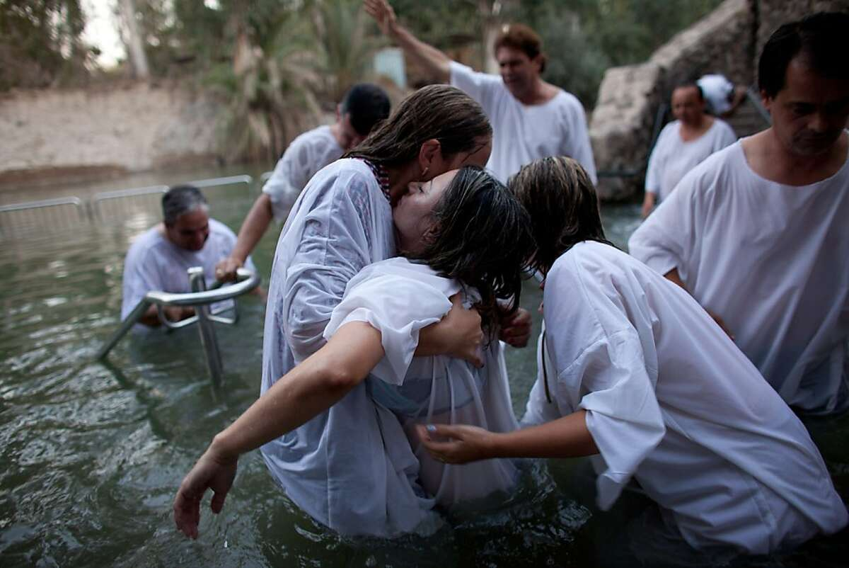 Christian pilgrims take part in a group baptism in the waters of the Jordan River on October 3, 2012 at Yardenit in northern Israel. An estimated 100,000 Christian worshippers make their pilgrimage to the Holy Land each year and one of their most sacred rituals is being immersed in the biblical river where, according to Christian beliefs, Jesus Christ was baptised by John the Baptist.