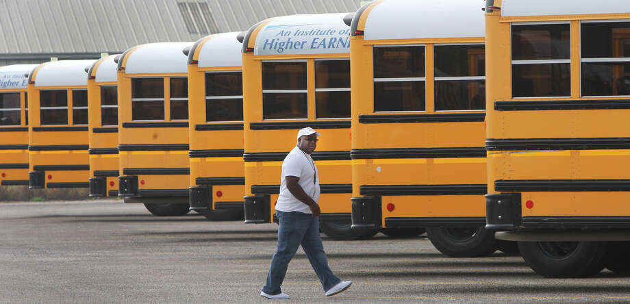 Judson Independent School District bus driver John Warren walks past buses at the Judson ISD bus barn Friday October 5, 2012. Warren was the driver of a school bus that crashed with a San Antonio Independent School District bus last Monday October 1, 2012 in front of Wagner High School. The driver of the SAISD bus, Dolores Martinez,63, died at the crash after losing control of her bus on Foster road. Warren has been credited with avoiding what Judson ISD spokesman Steven Linscomb said might have been a bigger tragedy. Photo: JOHN DAVENPORT, San Antonio Express-News / ©San Antonio Express-News/Photo Can Be Sold to the Public