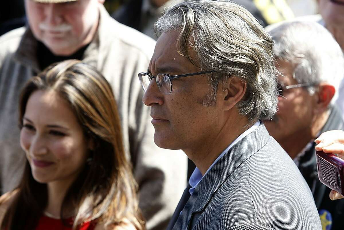 Eliana Lopez (in red) and her husband Ross Mirkarimi (right) listen to people rallying in his support in front of the steps of city hall in San Francisco, Calif., on Monday, September 17, 2012.