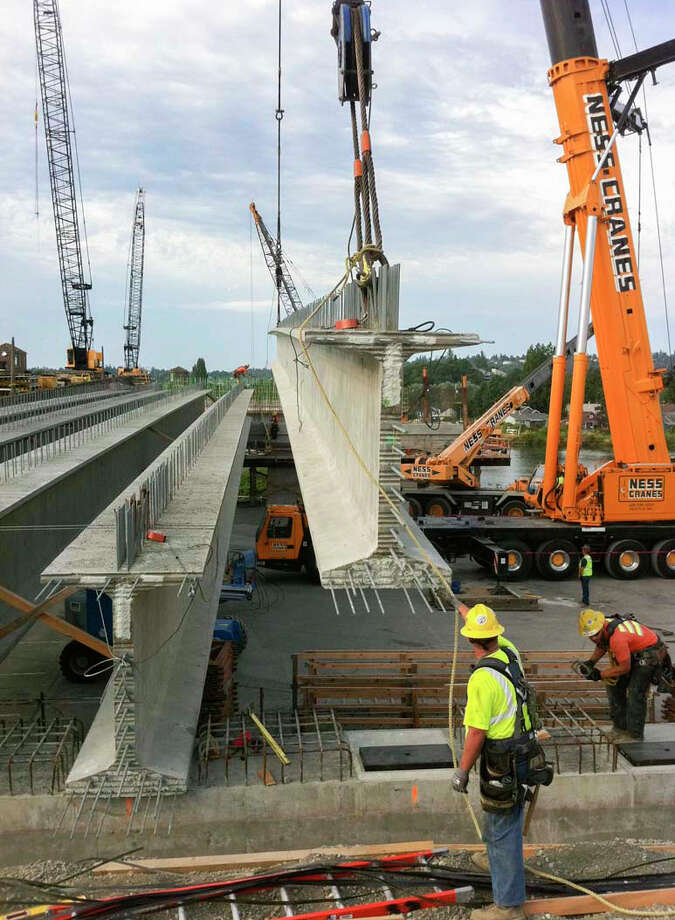 Workers guide a girder into place where the new bridge's north approach is being built. Photo: John Stamets