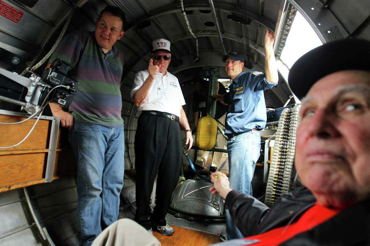 Members of the 8th Air Force Reunion group including, from left, Ivan Rasmussen, Joe Garber from Ormond Beach, FL, 89, of the 96th BG, Load Master Andrew Stample, and Joe Urice from Kerrville, 88, of the 100th BG, told stories as they waited out a weather delay before they got to ride on the WWII B-17G bomber