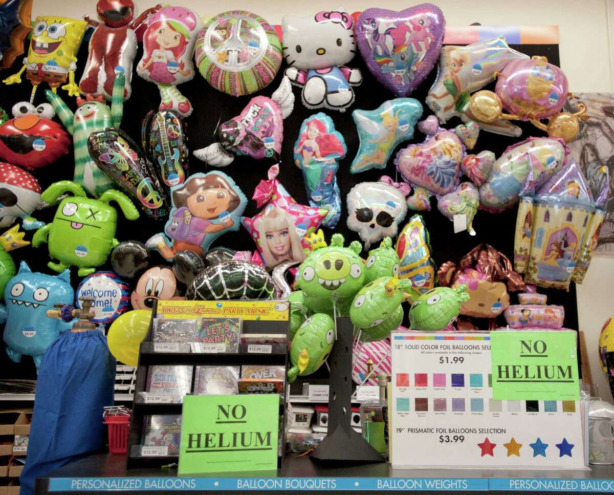Signs informing customers of a helium shortage are posted at a party balloon filling station, Wednesday, Oct. 3, 2012, at a Party City location in San Antonio.