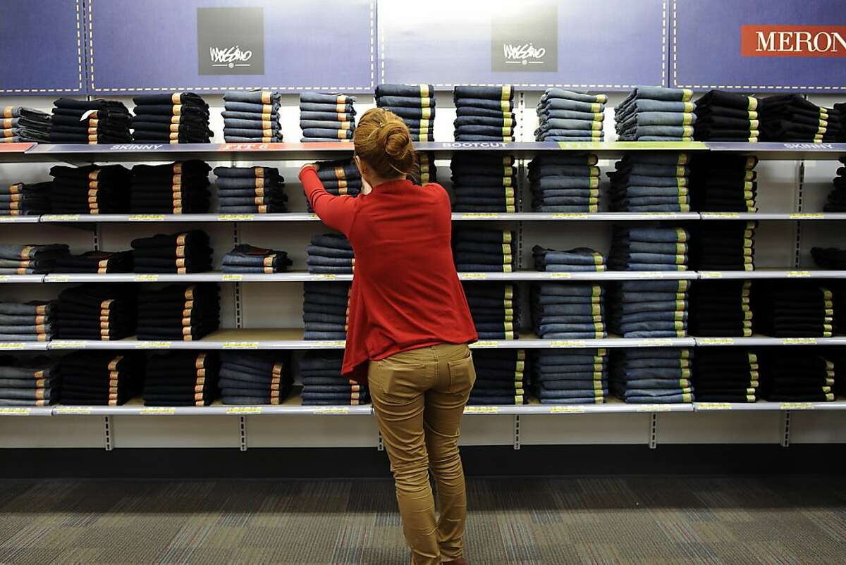 An employee fills up a wall display of womens jeans at the new CityTarget store, which is set to open on the 14th, at the renovated Metreon in San Francisco, Calif., Tuesday October 2nd, 2012.