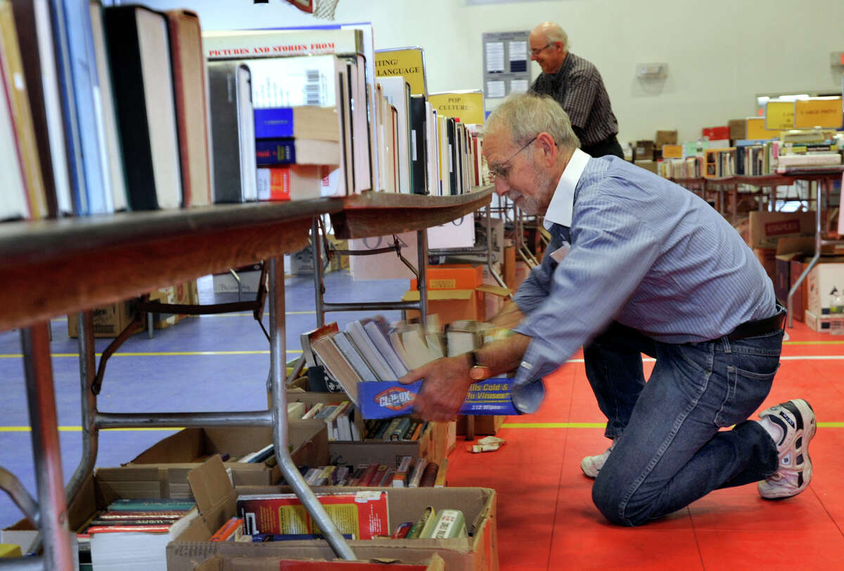 Robert Feinson, co-chairman of the annual Friends of Danbury Library Book Sale, joins volunteers doing last-minute preparations Friday for this weekends book sale, which goes through Monday. The Exchange Club of Danbury will be selling refreshments.