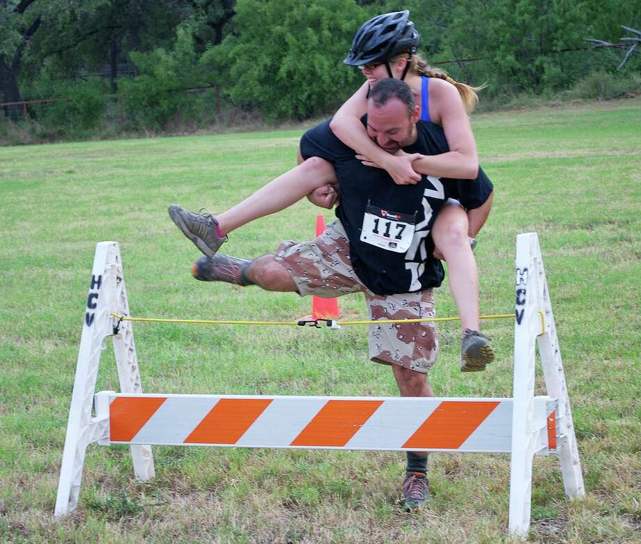 Fred Duncan carries event organizer Kristyn Bacon over a barrier during the Wife- and Partner-Carrying Contest Aug. 25 in Hill Country Village. Photo: Courtesy Photos