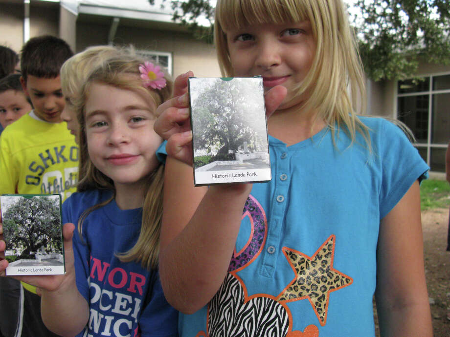 Lamar Elementary School students Olivia Scheffel (left) and Heidi Tabbert show off decks of educational cards about Landa Park. Photo: Zeke MacCormack, San Antonio Express-News