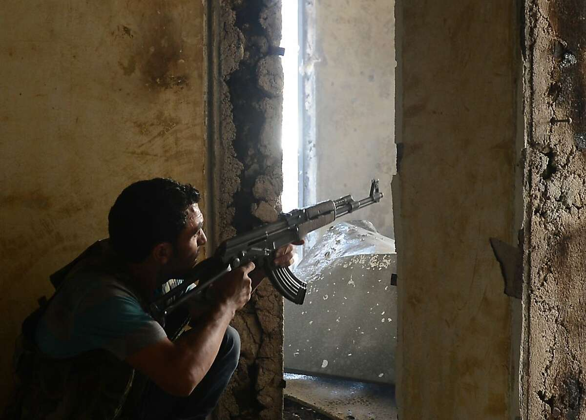 A Syrian rebel aims his weapon during clashes with forces in the Saif al-Dawla district of Aleppo.
