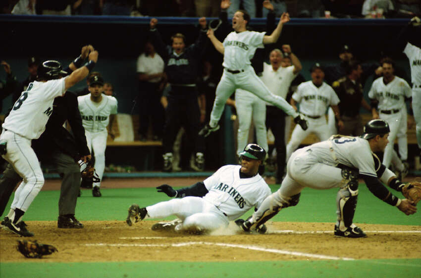Ken Griffey Jr. slides into home as teammates begin to celebrate the Mariners' win over the New York Yankees in Game 5 of the 1995 AL Division Series on Oct. 8, 1995.