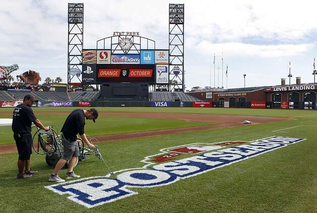 Brian Goodrich (left) and Jeff Winsor paint the postseason logo on the field at AT&T Park for Game 1 of the playoffs. Photo: Paul Chinn, The Chronicle