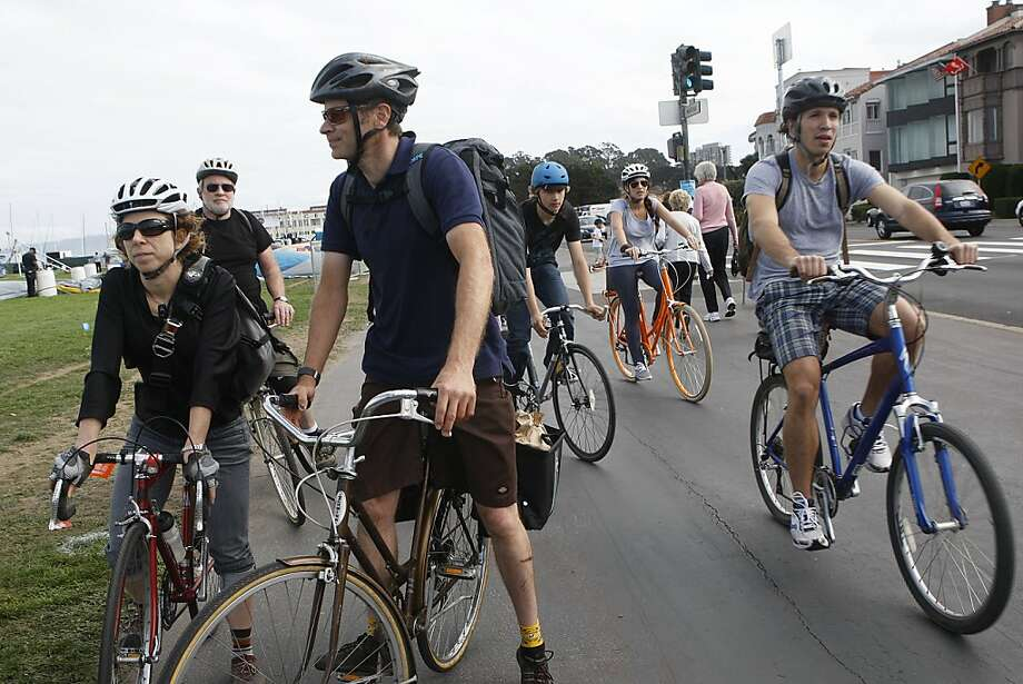Joan Wright (left) and Jason Ward (center) decide where to park at the Marina Green after arriving with their bikes via the Oakland ferry. Photo: Liz Hafalia, The Chronicle