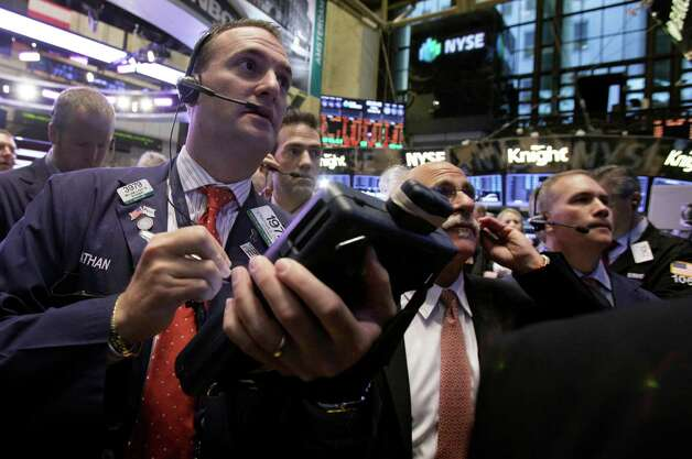 Jonathan Corpina, left, works with fellow traders on the floor of the New York Stock Exchange Friday, Oct. 5, 2012. Stocks are rising in early trading on Wall Street after the government reported that the U.S. unemployment rate fell below 8 percent for the first time in almost four years. (AP Photo/Richard Drew) Photo: Richard Drew