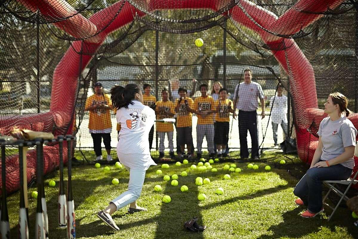Volunteer coach Laura Podolak (seated) assists batter Monica Seles during a San Francisco RBI softball practice.