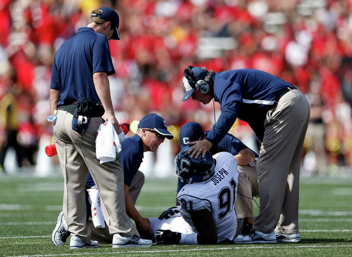 In this photo taken Saturday, Sept. 15, 2012, Connecticut defensive end Jesse Joseph (91) is tended to after injuring himself in the second half of an NCAA college football game against Maryland in College Park, Md. Joseph has a torn left Achilles tendon and will miss the remainder of the football season. (AP Photo/Patrick Semansky)