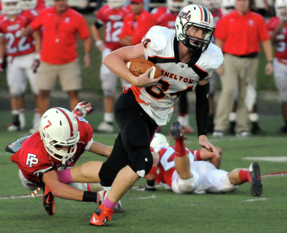 Shelton's Kyle Drost carries as Prep's Kevin Kirshner tackes as Fairfield Prep hosts Shelton High School in a football game at Fairfield University's Alumni Field in Fairfield, Conn., Oct. 5, 2012. Photo: Keelin Daly / Stamford Advocate