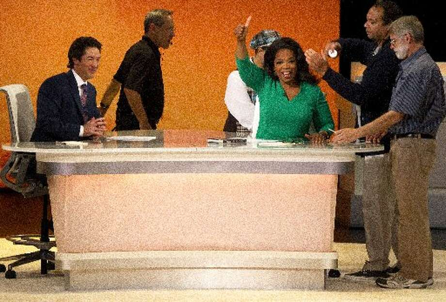 Joel Osteen and Oprah Winfrey are prepped before the cameras roll for the Oprah Winfrey Network at the The Hobby Center