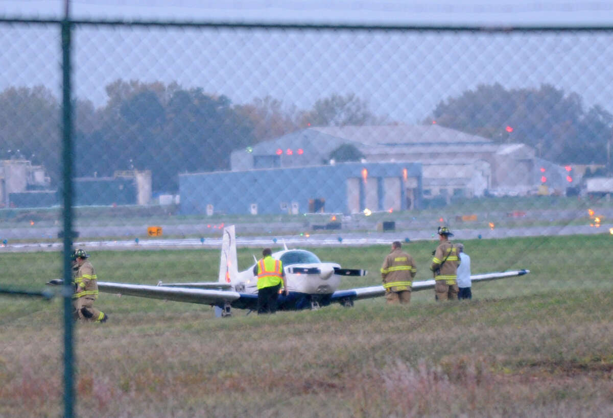 Albany International Airport Emergency personnel attend to a small aircraft at the end of the southern runway Friday evening, Oct. 5, 2012. (Will Waldron / Times Union)