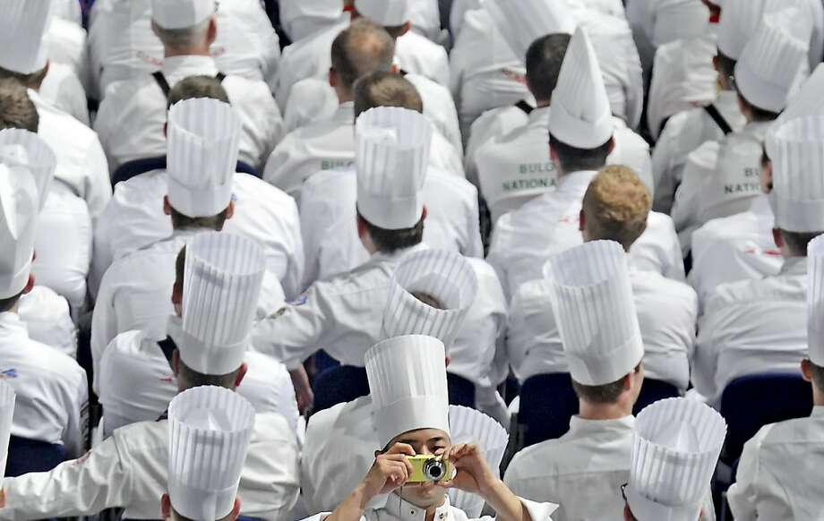 A cook takes photos during the opening ceremony of the International Exhibition of Culinary Art (IKA) also known as the Culinary Olympics IKA in Erfurt, central Germany, on Friday, Oct. 5, 2012. About 1,600 chefs and pastry chefs and their support teams from 50 countries transform the fairgrounds into a platform of finest culinary art Oct. 5-10, 2012. 36 national teams, 28 national youth teams, 8 national military teams and 14 community catering teams from all over the world take part at the competitions. The Culinary Olympics is the most important event for chefs and cooks from all over the world. (AP Photo/Jens Meyer) Photo: Jens Meyer, Associated Press