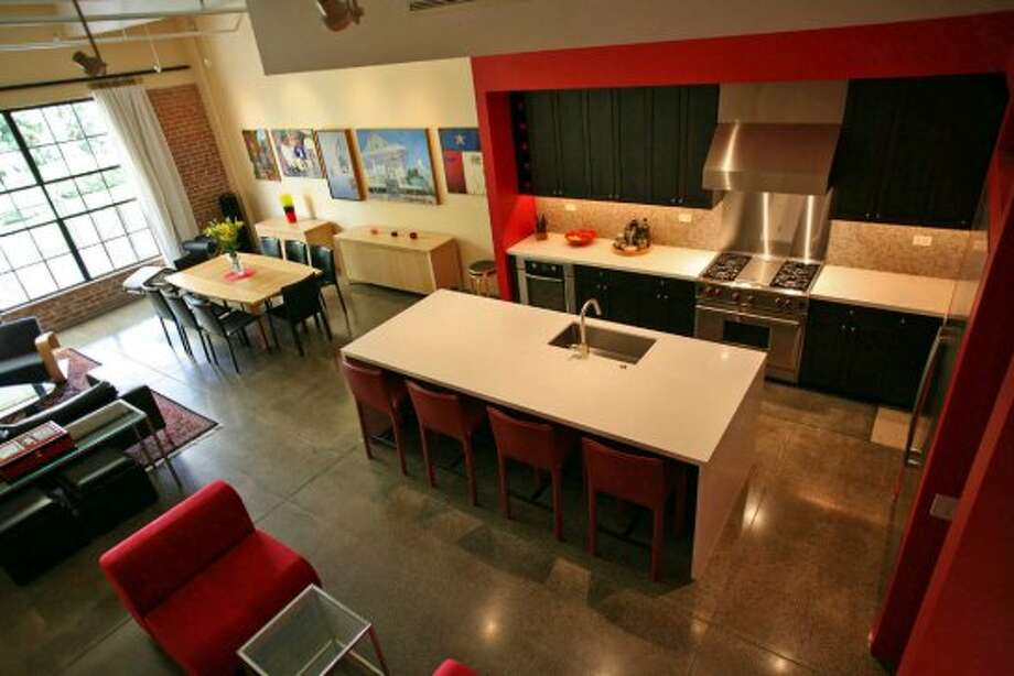 The kitchen gets one corner of the open area on the first floor;ÊÊ the rest of the room contains a dining table with seating for eight, a sofa and two chairs arranged around a glass table and a pair of red chairs in a casual area.