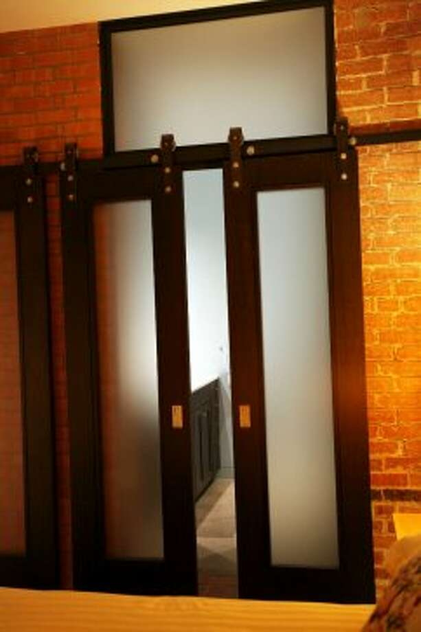 The steel barn-style doors in a second bedroom were custom-made and slide on a track.