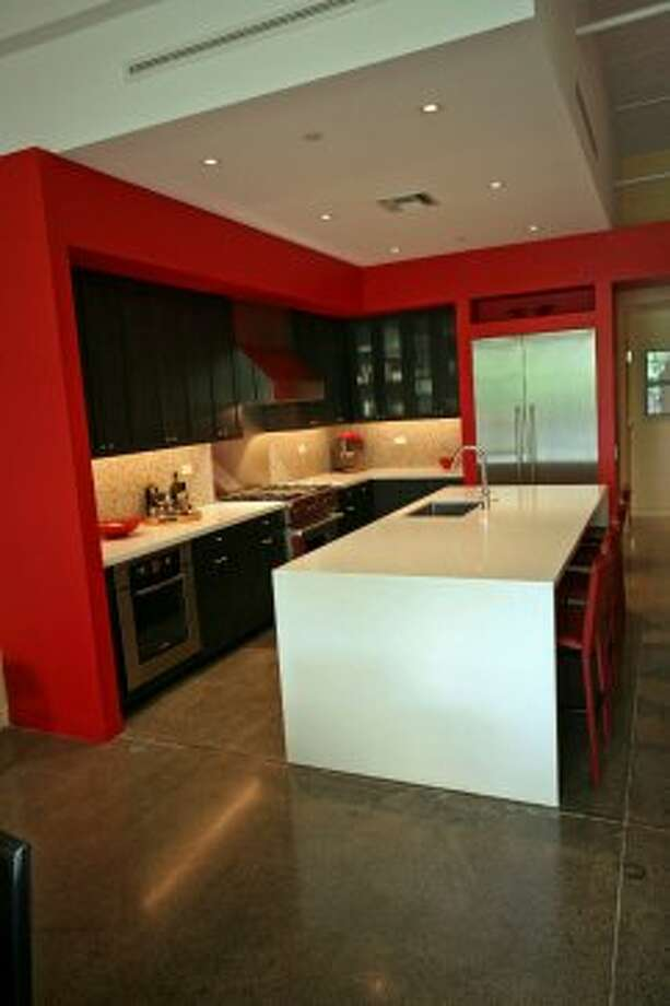 Red paint enlivens the kitchen, in a corner of the first-floor open area; the island can seat four people.