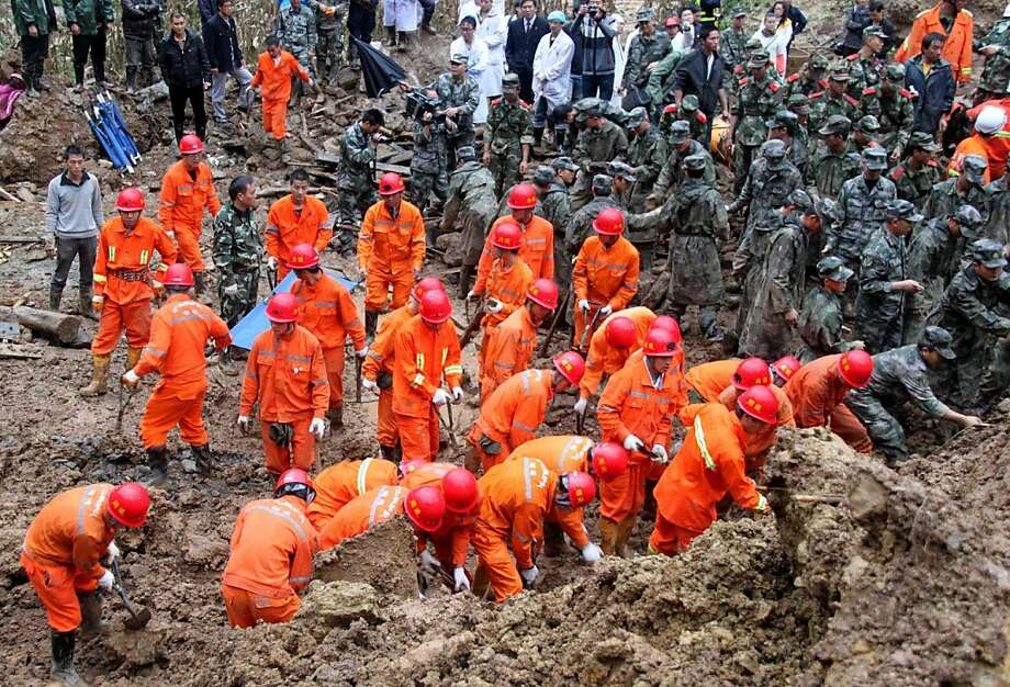 In this Oct. 4, 2012 photo provided by China's Xinhua News Agency,  rescuers search for victims at the site where a landslide occurred in the village of Zhenhe, Yiliang County, southwest China's Yunnan Province.  All 18 elementary school students buried in a landslide were confirmed dead Friday, while one other person also died after a hillside collapsed and smothered part of a village in mountainous southwestern China. (AP Photo/Xinhua, Xie Duming) NO SALES Photo: Xie Duming, Associated Press