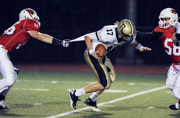 At center, Trumbull quarterback Nick Roberts # 17 gets sacked by Greenwich defenders, Jack Wynne, left, # 56, and Alex McGee # 58 during the boys high school football game between Greenwich High School and Trumbull High School at Greenwich, Friday afternoon, Oct. 5, 2012. Photo: Bob Luckey / Greenwich Time