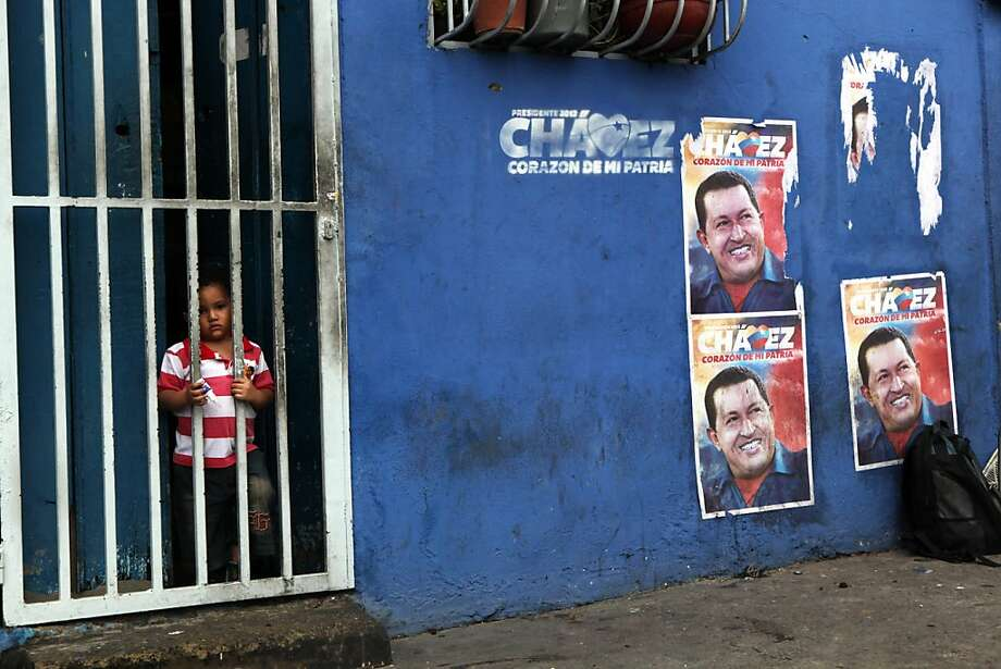 Santiago, 2, peeks out from the gate on his home's doorway where posters of Venezuela's President Hugo Chavez cover a wall in Caracas, Venezuela, Friday, Oct. 5, 2012. Venezuelans will head to the polls Sunday to vote in their country's presidential election, deciding on whether to keep Chavez or seek change. (AP Photo/Rodrigo Abd) Photo: Rodrigo Abd, Associated Press
