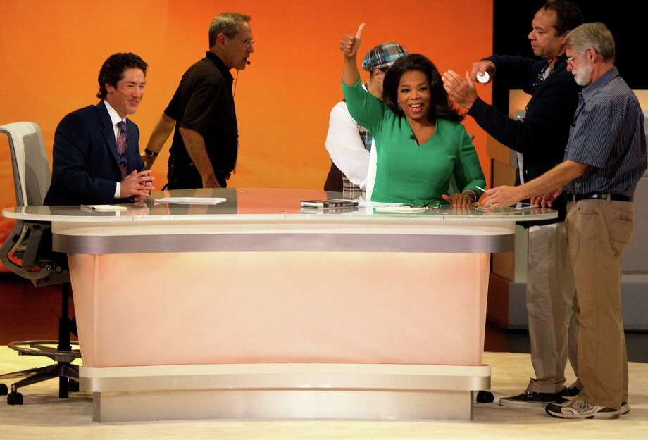 Joel Osteen grins as Oprah Winfrey gives the audience a thumbs-up while she is prepped for the taping of her show on Friday. Photo: Cody Duty / © 2012 Houston Chronicle
