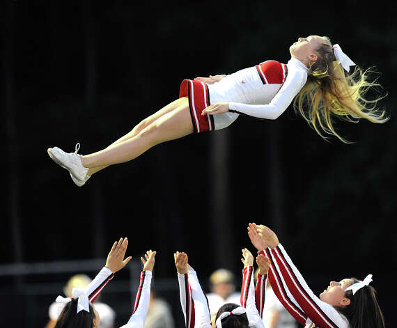 GHS cheerleader Dakota Hirsch, 13, a freshman, flys through the air during a cheer at the start of the boys high school football game between Greenwich High School and Trumbull High School at Greenwich, Friday afternoon, Oct. 5, 2012. Photo: Bob Luckey / Greenwich Time