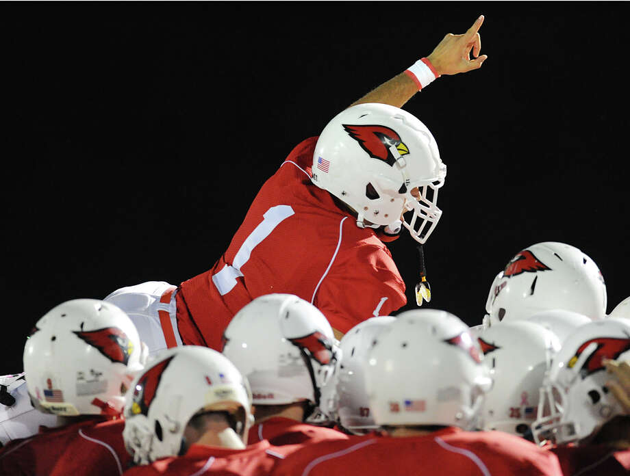 Vincent Ferraro # 1 of Greenwich gives the # 1 sign as he jumps atop a huddle of his teammates during the boys high school football game between Greenwich High School and Trumbull High School at Greenwich, Friday afternoon, Oct. 5, 2012. Photo: Bob Luckey / Greenwich Time