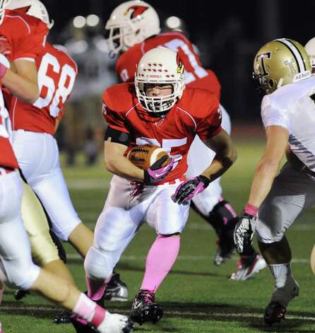Running back Mark Bernstein # 35 of Greenwich finds a hole in the Trumbull defense during the boys high school football game between Greenwich High School and Trumbull High School at Greenwich, Friday afternoon, Oct. 5, 2012. At right is Thomas Hayduk # 7 of Trumbull. Photo: Bob Luckey / Greenwich Time