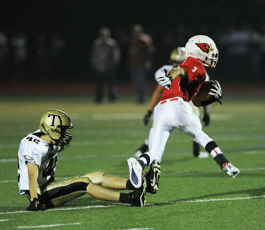 At right, Austin Longi # 3 of Greenwich jukes a Trumbull defender during the boys high school football game between Greenwich High School and Trumbull High School at Greenwich, Friday afternoon, Oct. 5, 2012. Photo: Bob Luckey / Greenwich Time