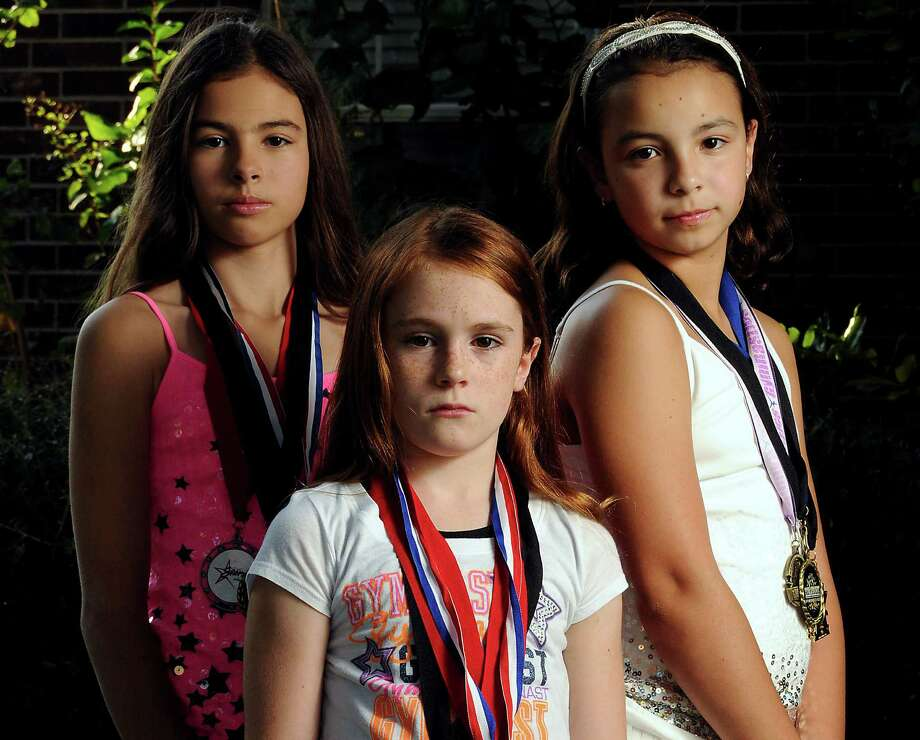 Among the young gymnasts who lost out on a chance to compete in Florida and pay a visit to Disney World were, from left, Hannah Tillinger, 11,  Rilee Dallison, 9, and Megan Martinez, 10. (Dave Rossman/Chronicle)