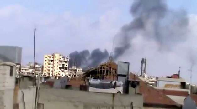 In this image taken from video obtained from the Shaam News Network, which has been authenticated based on its contents and other AP reporting, smoke rises from houses due to government shelling in Homs, Syria, on Friday, Oct. 5, 2012. (AP Photo/Shaam News Network via AP video) Photo: Anonymous
