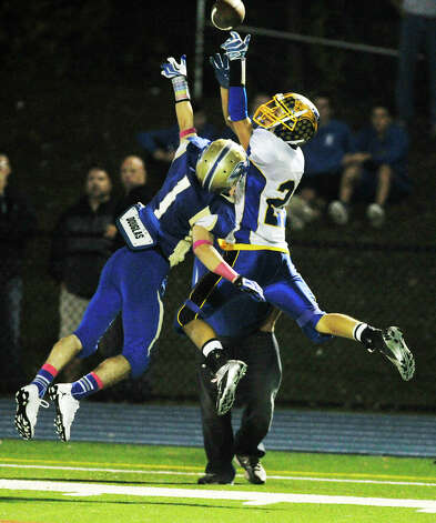 Brookfield's Nick Biasetti attempts to catch the ball while under pressure from Newtown's Justin DeVellis during their game at Newtown High School on Friday, Oct. 5, 2012. Newtown won, 35-7. Photo: Jason Rearick / The News-Times