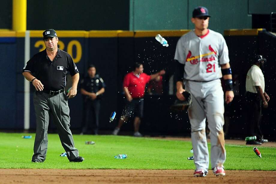 Umpire Rob Drake and Cardinals first baseman Allen Craig have backs turned to the bottles and cups being thrown onto the field by angry Braves fans. Photo: Scott Cunningham, Getty Images